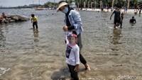Guna mencegah penyebaran virus Corona, tampak sejumlah wisatawan mengenakan masker maupun face shield atau pelindung wajah saat berkunjung ke Pantai Ancol.