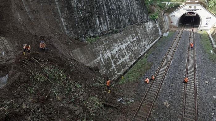 Sejumlah pekerja  memindahkan material longsoran yang menutupi jalur Kereta Api (KA), di Terowongan Kebasen, Banyumas, Jateng, Kamis (29/10/2020). Hujan lebat mengakibatkan longsor yang sempat menimbun jalur KA di terowongan Kebasen, Banyumas, Jateng, pada Rabu (28/10) malam pukul 22.50 WIB, dan menyebabkan sejumlah perjalanan KA sempat terganggu. ANTARA FOTO/Idhad Zakaria/nz.
