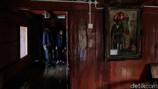 Sebuah lukisan tampak menggantung di salah satu sisi dinding di dalam rumah tersebut.
