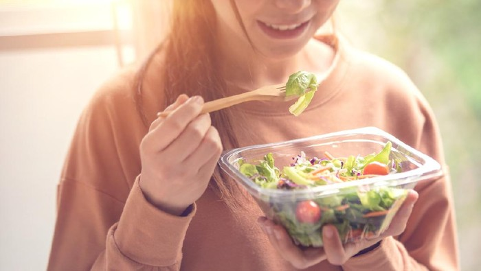 closeup woman eating healthy food salad, focus on salad and fork