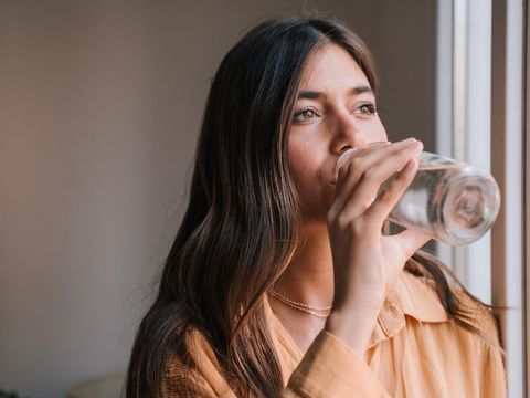 young beautiful woman by the window at home drinking water. Lifestyle