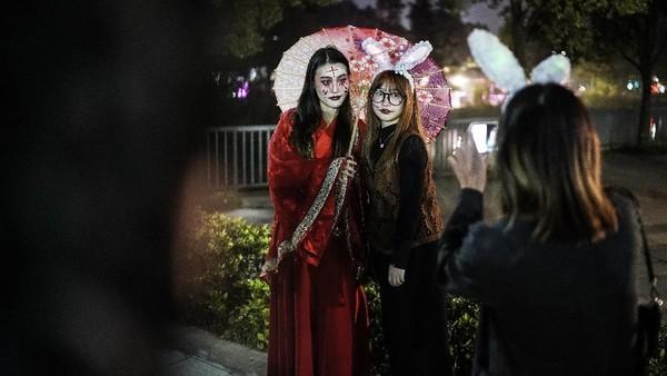 Mereka menyaksikan parade di taman hiburan Gappy Valley Wuhan pada Kamis (30/10/2020) malam.