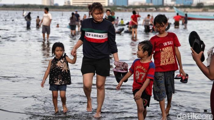 Warga bermain di kawasan Pantai Marunda, Jakarta Utara, Kamis (29/10/2020). Menurut ketenangan warga, Pantai Marunda merupakan wisata alternatif yang murah meriah untuk menghabiskan waktu libur panjang bersama keluarga.