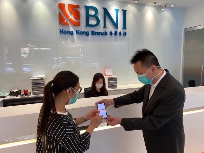 Pegawai BNI sedang menjelaskan fitur International Remittance di Kantor Cabang BNI Hongkong