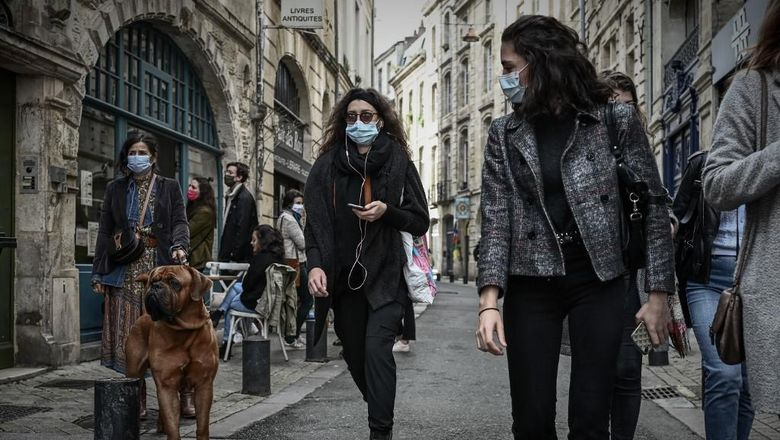 Pedestrians wearing protective face masks walk in a street of Bordeaux on October 29, 2020, as a new Covid-19 lockdown comes into effect at midnight. - French President announced on October 28 a new lockdown aimed at halting an alarming acceleration of Covid-19 cases, to take effect from October 29 night until