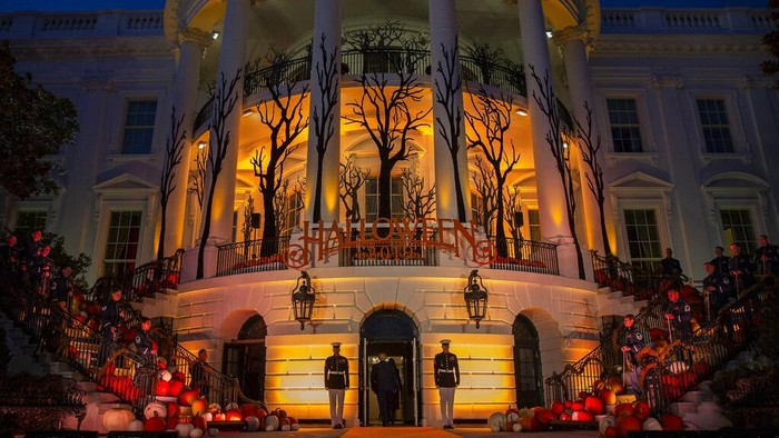 President Donald Trump talks with first lady Melania Trump as they greet trick-or-treaters on the South Lawn during a Halloween celebration at the White House, Sunday, Oct. 25, 2020 in Washington. (AP Photo/Manuel Balce Ceneta)