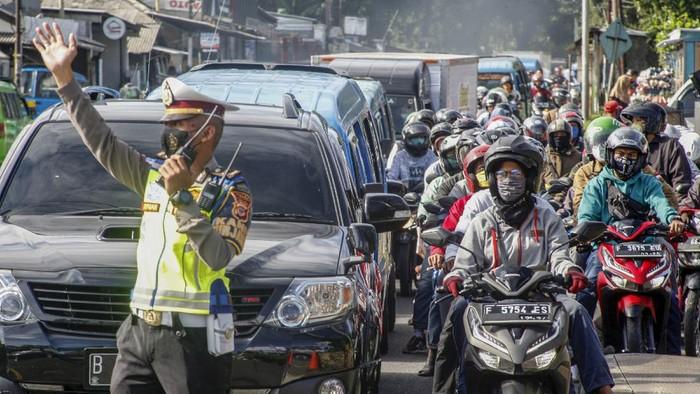 Polisi mengatur lalu lintas kendaraan yang  memadati ruas jalan jalur Wisata Puncak,  Kabupaten Bogor, Jawa Barat,  Sabtu (31/10/2020). Pada cuti bersama serta libur panjang Maulid Nabi Muhammad SAW hari ke-empat jalur wisata Puncak Bogor masih dipadati kendaraan wisatawan, Sat Lantas Polres Bogor memberlakukan rekayasa lalu lintas sistem satu jalur atau one way untuk mengurai kepadatan kendaraan. ANTARA FOTO/Yulius Satria Wijaya/hp.