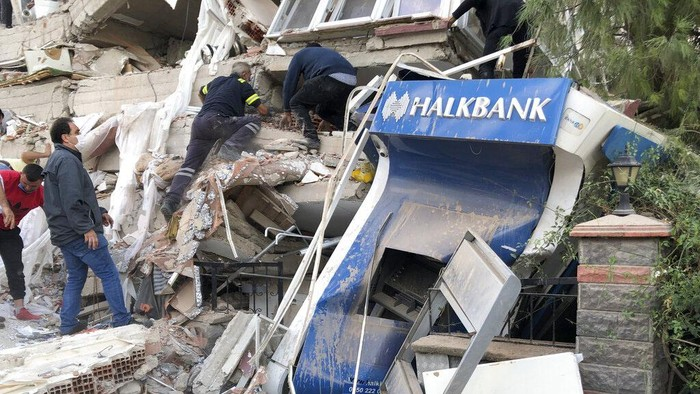 Rescue workers and local people try to reach residents trapped in the debris of a collapsed building, in Izmir, Turkey, Friday, Oct. 30, 2020, after a strong earthquake in the Aegean Sea has shaken Turkey and Greece. Turkeys Disaster and Emergency Management Presidency said Fridays earthquake was centered in the Aegean at a depth of 16,5 kilometers (10.3 miles) and registered at a 6.6 magnitude.(AP Photo/Ismail Gokmen)