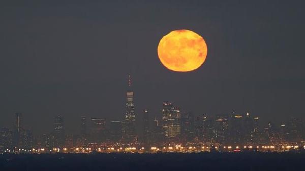 Full Hunters Moon terlihat jelas di Manhattan, New York pada 31 Oktober 2020. Bulan tampak berwarna merah, oranye dan kuning ini terlihat begitu indah. (Corbis via Getty Images/Gary Hershorn)