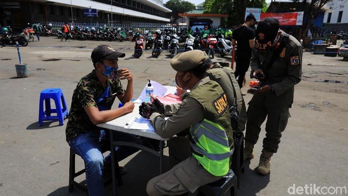 Petugas Satpol PP melaksanakan operasi yustisi di kawasan Kota Tua, Jakarta, Minggu (1/11/2020). Meski kini DKI Jakarta berada pada Pembatasan Sosial Berskala Besar (PSBB) masa transisi, namun operasi yustisi tetap digalakan guna mendisiplinkan masyarakat demi menekan penyebaran COVID-19.