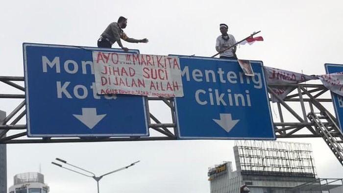Wadirlantas Polda Metro AKBP Hari Purnomo membujuk pemasang spanduk di tiang rambu.