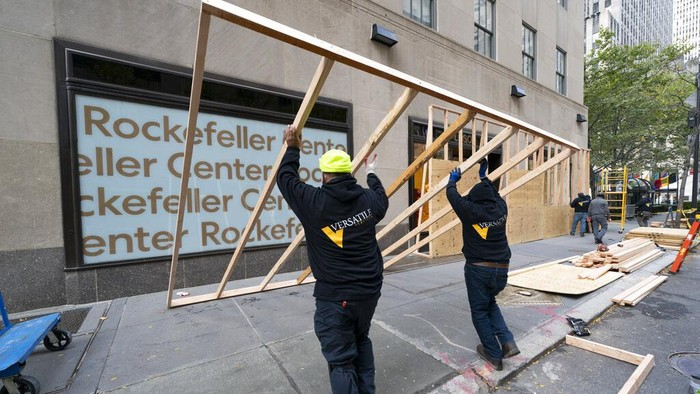 Workers board up Bergdorf Goodman department store, Monday, Nov. 2, 2020, in New York ahead of Tuesday's contentious presidential election. The moves come as retailers are trying to protect themselves against possible civil unrest in a year that has seen widespread protests over social justice that sometimes became violent. (AP Photo/Mark Lennihan)