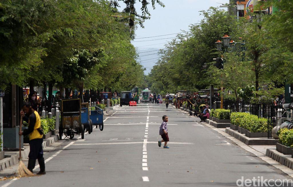 Sejumlah pengunjung berfoto ditengah jalan Malioboro saat uji coba management rekayasa lalu lintas kawasan pedestrian Malioboro, Yogyakarta, Selasa (3/11/2020). Pembatasan kendaraan bermotor yang masuk Jalan Malioboro membuat pengunjung leluasa menikmati kawasan pedestrian malioboro