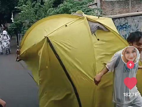Pasangan pengantin yang lari karena hujan saat menjalani foto prewedding