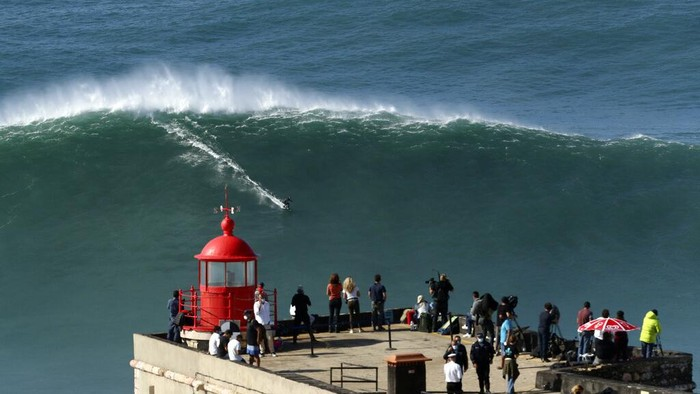 A surfer rides a wave during a tow surfing session at Praia do Norte or North Beach in Nazare, Portugal, Thursday, Oct. 29, 2020. A big swell generated earlier in the week by Hurricane Epsilon in the North Atlantic, reached the Portuguese west coast drawing big wave surfers to Nazare. (AP Photo/Pedro Rocha)