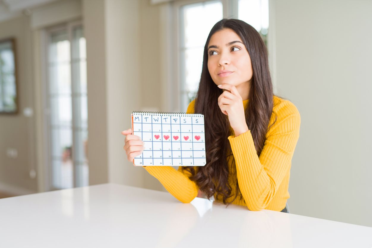 Young woman holding menstruation calendar serious face thinking about question, very confused idea