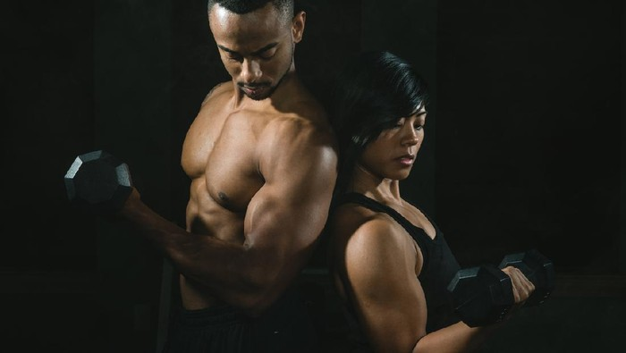 Young African American Couple Lifting Weights Together In Gym