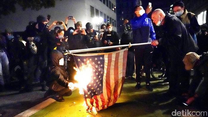 Seorang pengunjuk rasa menyalakan bendera Amerika dengan api saat demonstrasi Rabu, 4 November 2020, di Portland, Ore. Para demonstran turun ke jalanan berbagai kota dan wilayah di Amerika Serikat (AS) untuk menyerukan agar seluruh suara dalam pilpres AS dihitung hingga tuntas.