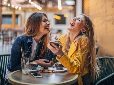 Girlfriends using Smartphone in Coffeeshop