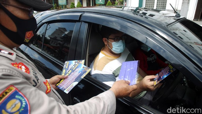 Petugas Kepolisian dari Polresta Kota Yogyakarta membagikan masker, hand sanitizer dan selebaran saat Operasi Zebra Progo 2020 kepada pengendara di Simpang Titik Nol Kilometer, Yogyakarta, Kamis (5/11/2020). Pembagian masker, hand sanitizer dan selebaran bertujuan untuk mencegah persebaran COVID-19 dan kampanye taat protokol kesehatan.
