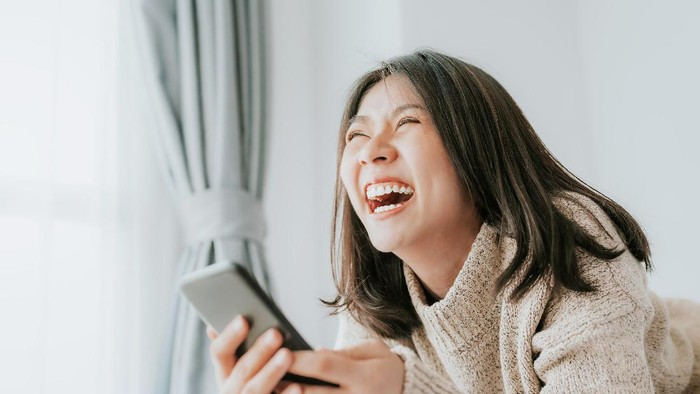 Happy Asian woman laughing while lying on the bed using smartphone mobile at home