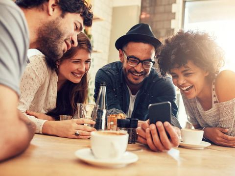 Portrait of cheerful young friends looking at smart phone while sitting in cafe. Mixed race people sitting at a table in restaurant using mobile phone.