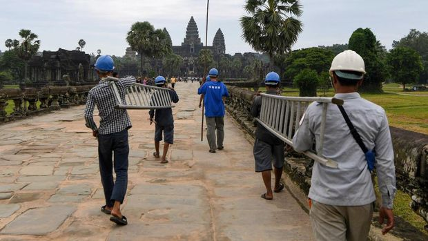 This photo taken on October 12, 2020 shows a gardener throwing down tree saplings removed from the exterior of the Angkor Wat temple in Siem Reap province. - Stacking a ladder against the towering spires of Cambodia's archaeological marvel Angkor Wat, a crack team of gardeners gingerly scales the temple's exterior to hack away foliage before it damages the ancient facade. (Photo by TANG CHHIN Sothy / AFP) / TO GO WITH Cambodia-archaeology-culture-conservation, FEATURE by Suy SE