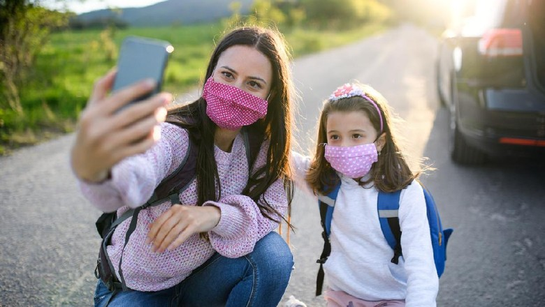 Mother with small daughter taking selfie with smartphone on trip outdoors in nature, wearing face masks.
