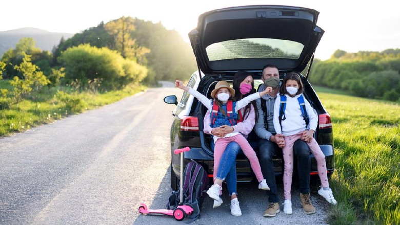 Front view of family with two small daughters on trip outdoors in nature, wearing face masks.