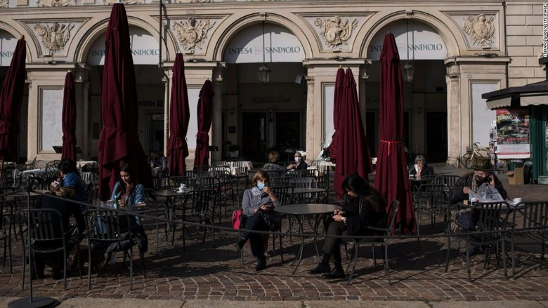 Orang memakai masker di Piazza San Carlo di Turin pada Kamis, sehari sebelum Italia memasuki lockdown.