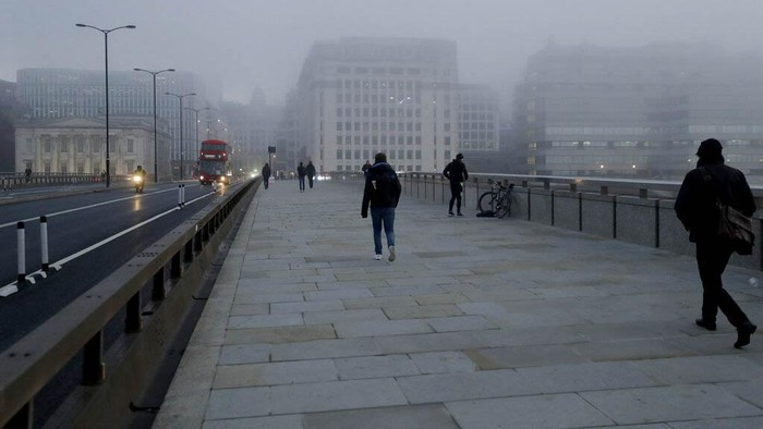 People walk over a foggy London Bridge towards the City of London financial district, on the first day of Britains second lockdown designed to save its health care system from being overwhelmed by people with coronavirus, in London, Thursday, Nov. 5, 2020. Britain joined large swathes of Europe in a coronavirus lockdown designed to save its health care system from being overwhelmed. Pubs, along with restaurants, hairdressers and shops selling non-essential items closed on Thursday until at least Dec. 2. (AP Photo/Matt Dunham)