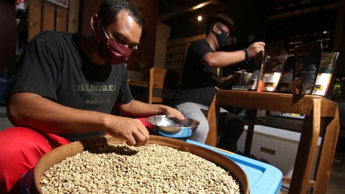 Pekerja melakukan proses foto produk kopi untuk dipasarkan secara daring di Kemiren, Banyuwangi, Jawa Timur, Jumat (6/11/2020). Pemilik Usaha Mikro, Kecil dan Menengah (UMKM) itu mengaku saat ini usaha pembuatan produk kopi mulai bangkit karena meningkatnya kunjungan wisatawan ke pusat oleh-oleh serta pemasaran produk yang dilakukan secara daring. ANTARA FOTO/Budi Candra Setya/wsj.