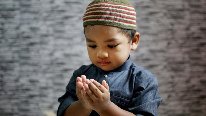 A Muslim young man is putting both palms together (Muslim way of praying) at home in Malaysia. He is wearing baju Melayu, a traditional Muslim menswear.