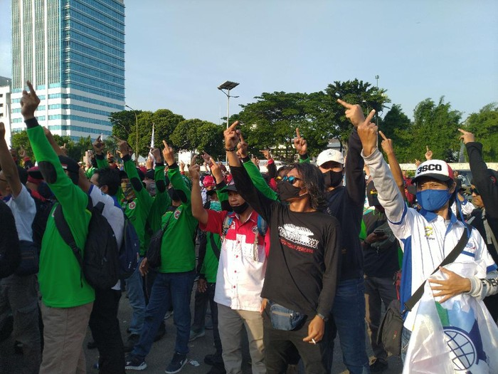 Massa buruh yang demo menolak UU Ciptaker di depan gedung DPR/MPR membubarkan diri. Mereka sempat mengacungkan jari tengah yang dianggap mereka sebagai simbol perlawanan (Sachril Agustin/detikcom)