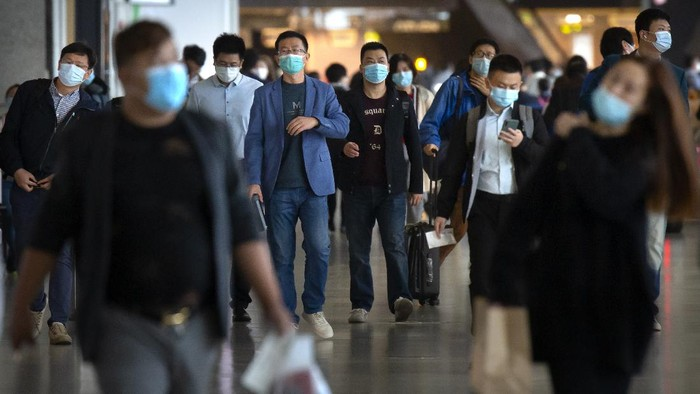 Travelers wearing face masks to protect against the coronavirus walk along a concourse at the Shanghai Hongqiao International Airport in Shanghai, Friday, Nov. 6, 2020. With the COVID-19 outbreak largely under control within its borders, air travel in China has mostly returned to pre-pandemic levels. (AP Photo/Mark Schiefelbein)