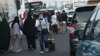 Seorang penumpang pesawat terpaksa harus berjalan kaki menuju bandara Soekarno Hatta sambil membawa kopernya di tengah massa yang memadati bandara sejak, Selasa (10/11) dinihari.