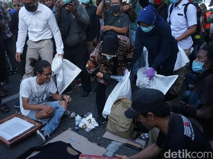 Wali Kota Surabaya Tri Rismaharini tiba-tiba mendatangi para pedemo tolak Omnibus Law di Taman Apsari. Ia memasuki kerumunan pedemo dan memunguti sampah.