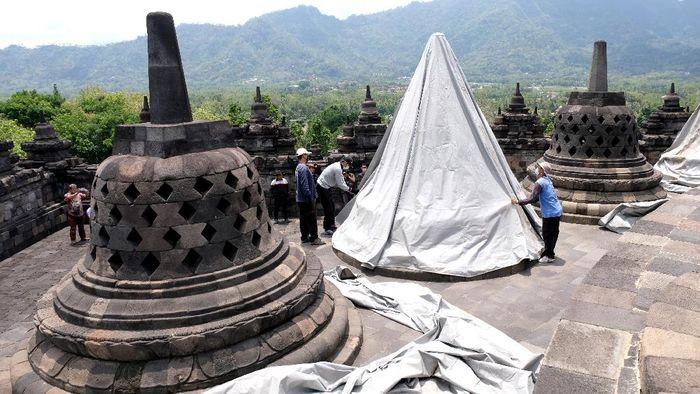 Sejumlah pekerja menutup stupa menggunakan terpaulin di kompleks candi Borobudur, Magelang, Jateng, Rabu (11/11/2020). Penutupan candi Borobudur oleh Balai Konservasi Borobudur (BKB) sebagai langkah antisipasi melindungi batu candi dari abu vulkanik jika gunung Merapi Erupsi. ANTARA FOTO/Anis Efizudin/hp.