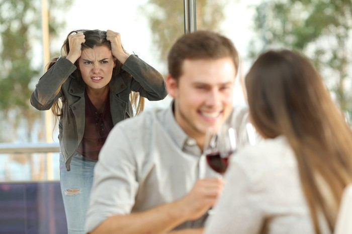 Disloyal boyfriend caught by his angry girlfriend dating with another girl in a restaurant