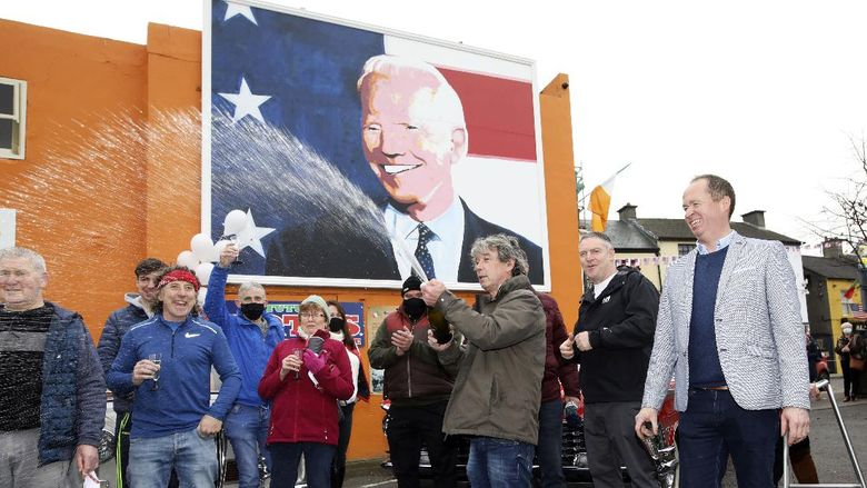 Joe Blewitt, a cousin of US Presidential candidate Joe Biden, celebrates in anticipation of the results of the US election as Biden edges closer to victory over Donald Trump, at a mural of Biden in his ancestral home of Ballina, Co. Mayo, Ireland, Saturday, Nov. 7, 2020. (AP Photo/Peter Morrison)