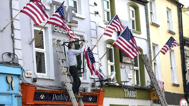 A shop owner puts a US flag up in Ballina, North West of Ireland Saturday, Nov. 7, 2020. Ballina is the ancestral home of US Presidential candidate Joe Biden. (AP Photo/Peter Morrison)