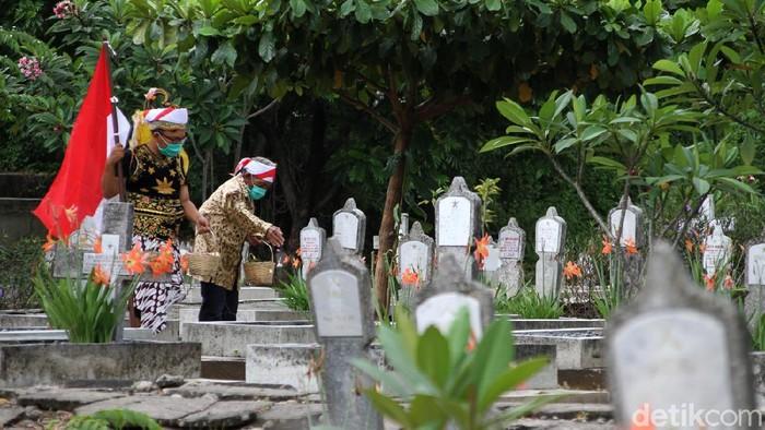 Mbah Min atau Ngadimin Citro Wiyono (88thn) ditemani penggiat sosial melakukan tabur bunga dan menceritakan kisah hidupnya kepada anak-anak di TMP Kusuma Bakti, Solo, Jawa Tengah, Rabu (11/11/2020).