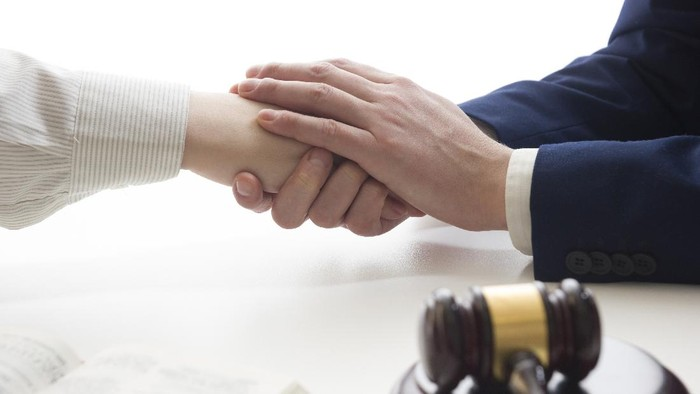 Hands of wife, husband signing decree of divorce, dissolution, canceling marriage, legal separation documents, filing divorce papers or premarital agreement prepared by lawyer. Wedding ring.