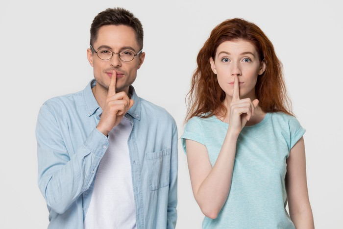 Young mute couple holding fingers on lips mouth to keep it quiet hush secret showing shh shush gesture for conspiracy silence looking at camera isolated on white grey blank studio background