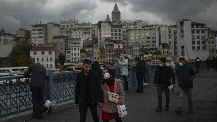 People, most wearing protective face masks to help protect against the spread of coronavirus, walk along Galata Bridge over the Golden Horn in Istanbul, Tuesday, Nov. 10, 2020. Turkeys government had urged the citys residents to limit their mobility and called on employers to offer workers flexible or staggered working hours and the possibility of working from homes. (AP Photo/Emrah Gurel)