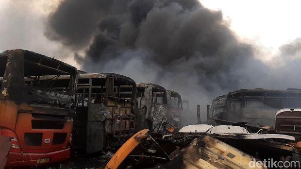 Kebakaran terjadi di lokasi penampungan bangkai bus Trans Jakarta di Desa Dramaga, Bogor. Puluhan bangkai bus nampak hangus terbakar.