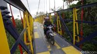 Pengendara melintas di Jembatan Gantung Mangunsuko, Dukun, Magelang, Jawa Tengah, Jumat (13/11/2020).
