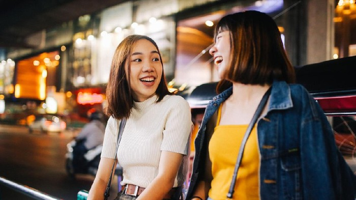 Vintage toned image of two young, Asian women, walking together, chatting, near Siam station on Bangkok Sukhumvit line. They're wearing casual street style clothing, enjoying the evening together.