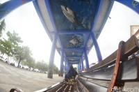 Wisatawan berfoto dengan latar dinding dan lantai jembatan yang dilukis dengan tema ragam biota laut di SkywalkPantaiBarat Pangandaran.