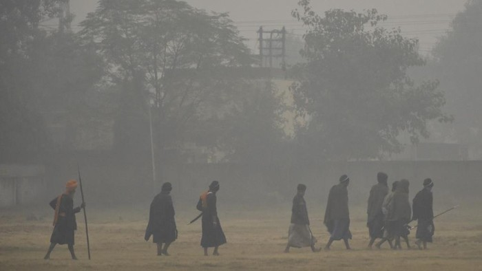 Sikh people walk along a field under heavy smog conditions after a Fateh Divas celebration a day after Diwali festival, in Amritsar on November 15, 2020. (Photo by NARINDER NANU / AFP)